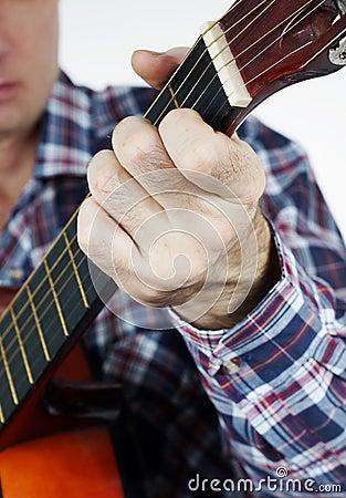 Man plays a chord on guitar