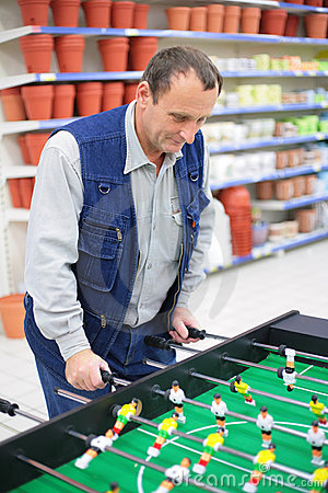 Man plays into  table football in store