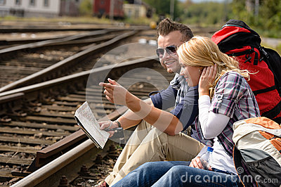 Man pointing direction with map on railroad