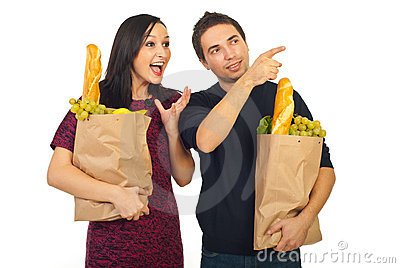 Man pointing to his amazed wife at shopping
