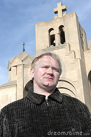 Man poses on church background