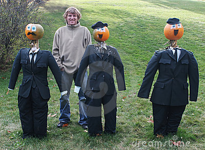 Man poses with pumpkin people in suits
