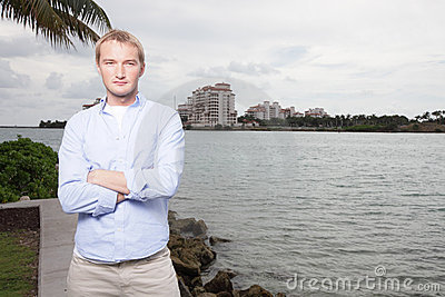 Man posing with arms crossed by the bay
