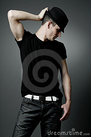 Man posing in black t-shirt and black hat.