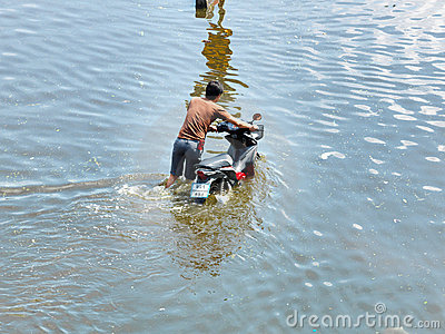 Man pouches motorbike through water Editorial Stock Image