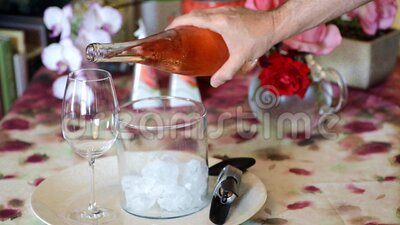 Man pouring french quality Rose wine to complete his delicious fish lunch. In his home stock video footage