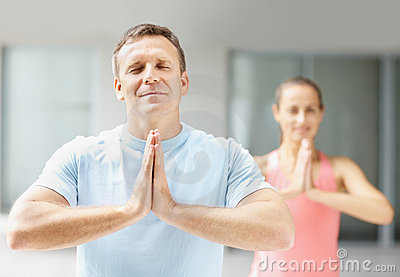Man practicing yoga at a gymnasium with a woman