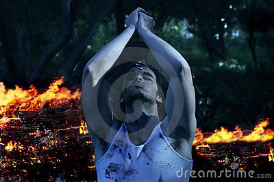 Man Praying with fire in background
