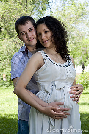 Man and a pregnant woman hugging in the park
