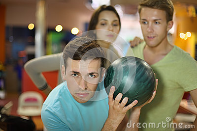 Man prepares to throw of ball; man and woman look