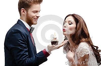 Man presents birthday sponge cake to his girlfriend
