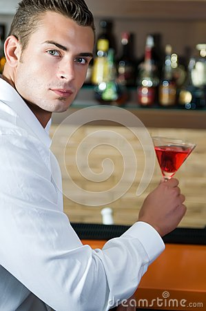 Man in a pub with red martini waiting