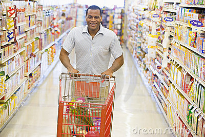 Man pushing trolley along supermarket aisle