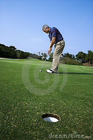 Man putting at golf course.