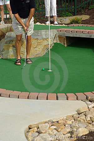 Man putting on a Putt Puut course.