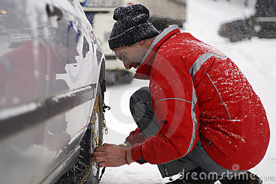 Man putting snow chains on car tire