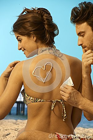 Man putting sunscreen on back of woman in swimsuit
