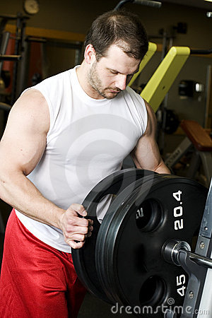 Man putting weights on bar in gym