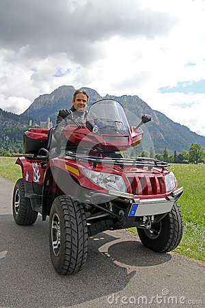 A man on quad before the mountains in Bavaria
