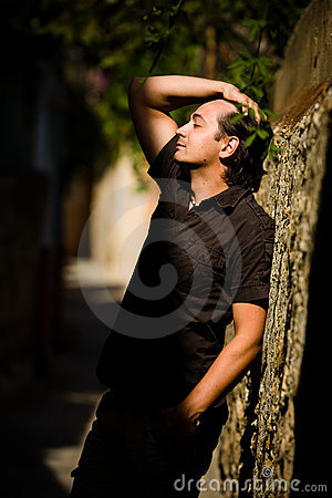 Man with raised hand leans wall in the street