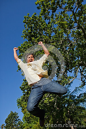 Man raising both of his arms and both of his legs as he jumps in
