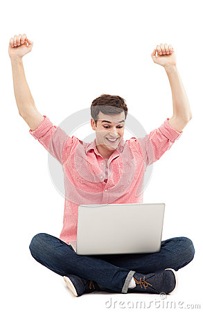 Man raising his arms in front of laptop