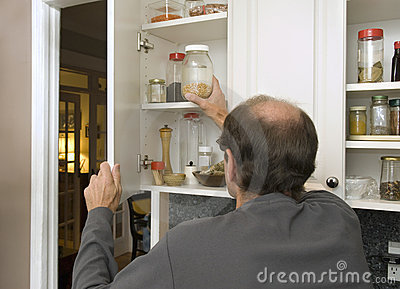 Man reaching for popcorn in empty cabinet