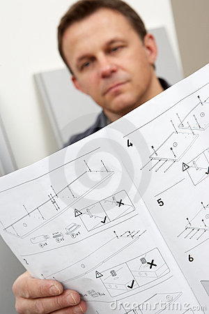 Man Reading Assembly Instructions For Flat Pack