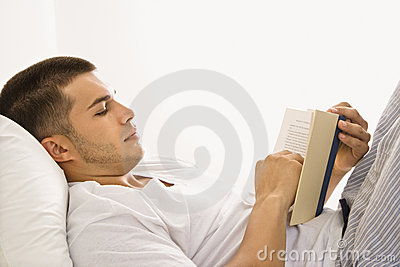 Man reading book in bed.
