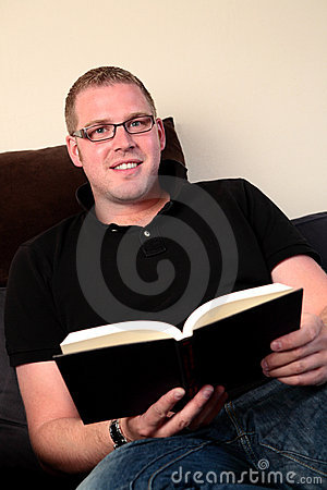 A Man Reading a Book at Home