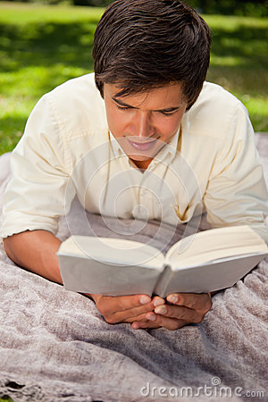 Man reading book while he lies on a blanket