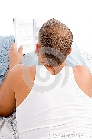 Man reading book while resting on matress bed