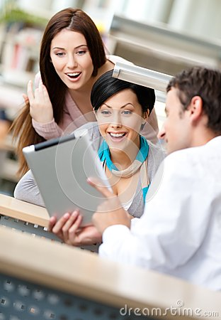 Man at the reading hall shows tablet to two women