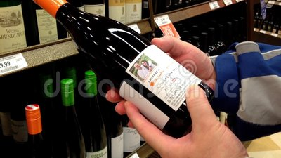 Man reading lable of red wine from the shelf. Shopping and choosing a bottle of wine from the large selection to buy, grabbing it from the display rack stock footage