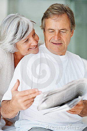 Man reading the news from the newspaper to a woman