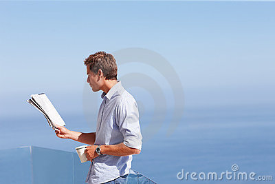Man reading a newspaper with blue sky at the back