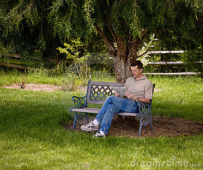 Man reading newspaper under tree