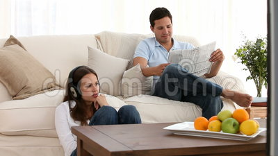 Man reading the newspaper while a woman listens to music Stock Photo