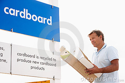 Man At Recycling Centre Disposing Of Cardboard