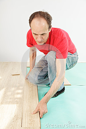 Man in red installing flooring