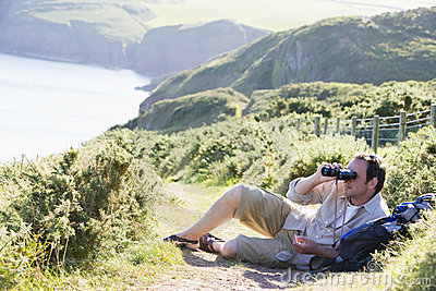 Man relaxing on cliffside path using binoculars