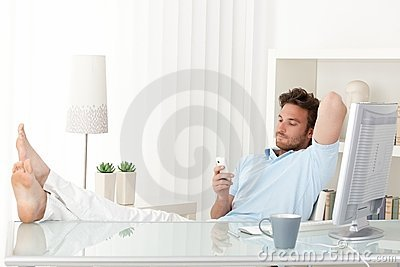 Man relaxing at desk, texting on phone