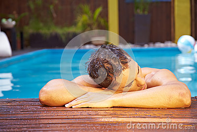 Man relaxing on edge of pool