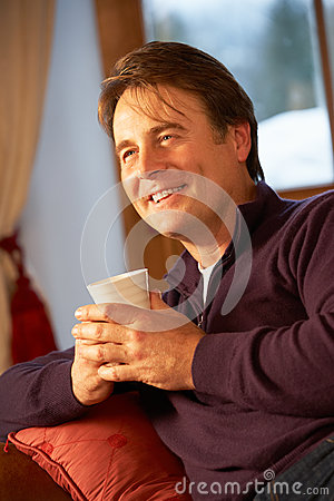 Man Relaxing With Hot Drink On Sofa Watching TV