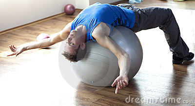 Man relaxing on large stability ball