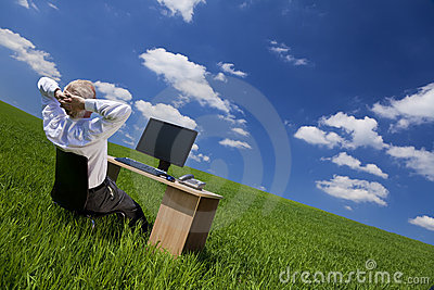 Man Relaxing At Office Desk In a Green Field