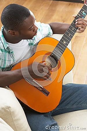 Man Relaxing Sitting On Sofa Playing Guitar