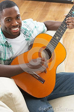Man Relaxing Sitting On Sofa Playing Guitar