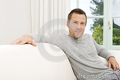 Man relaxing on sofa at home.