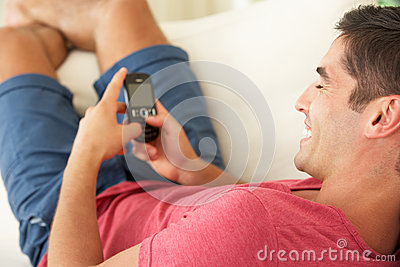Man Relaxing On Sofa Sending Text Message